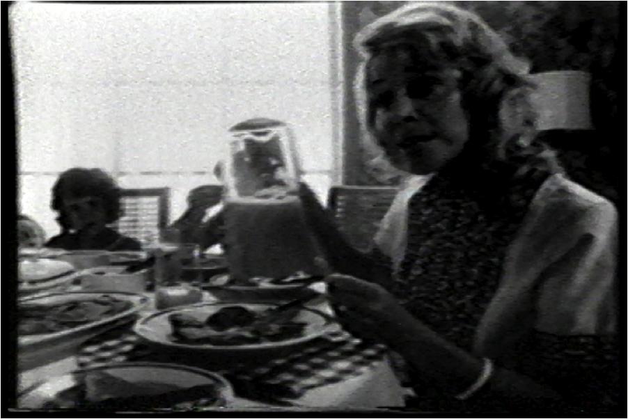 Image : Femme assise à la table avec sa famille, image tirée de la vidéo Femmes soyez, 1973.